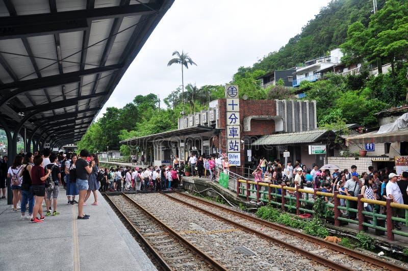 Туристы пересекая на железнодорожный путь наряду с улицей Shifen старой от станции Shifen, Тайваня стоковая фотография