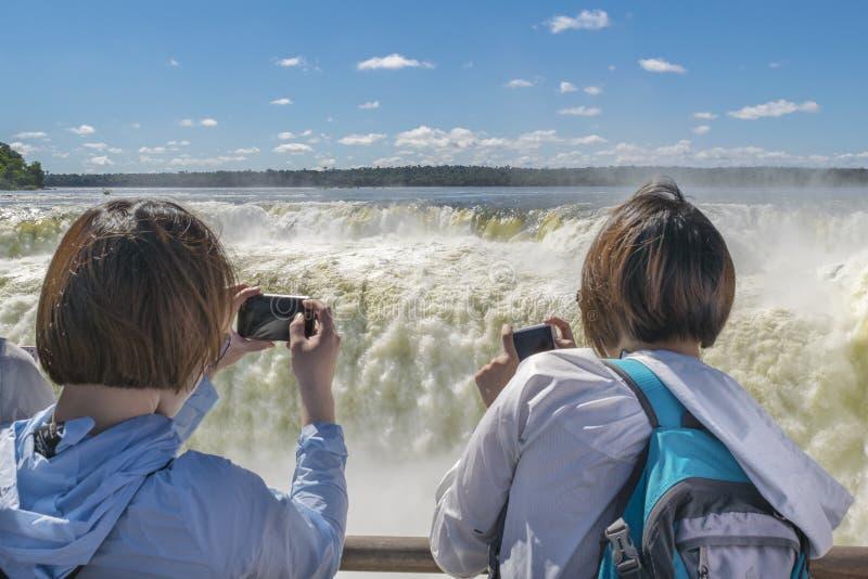 Туристы принимая фото горла дьявола на парк Iguazu стоковые изображения rf