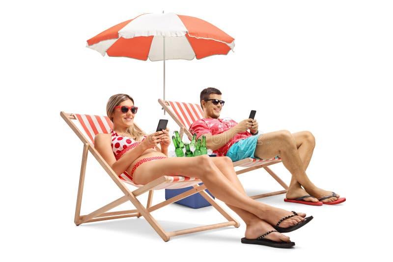 Туристы при телефоны сидя в шезлонгах стоковые изображения rf