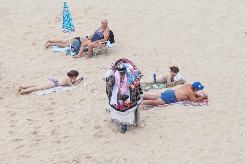 Туристы продавца улицы причаливая в пляже Sesimbra, Portuga стоковое изображение