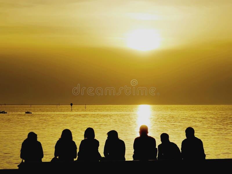 Туристы сидя на заходе солнца seashore наблюдая стоковое изображение