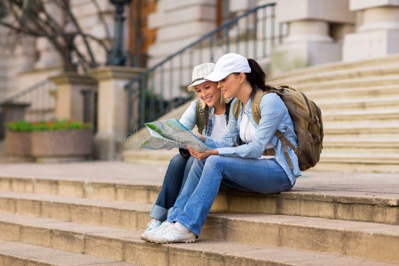 Туристы смотря карту стоковое фото