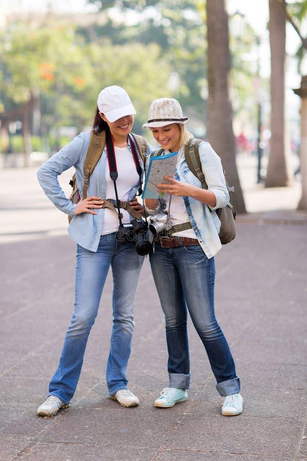 Туристы смотря карту стоковые изображения