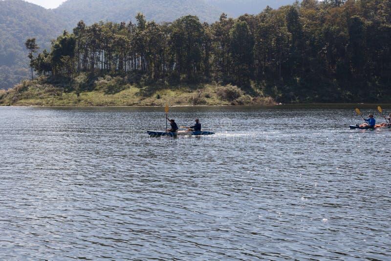 Туристы сплавляться на озере в горах стоковые фото