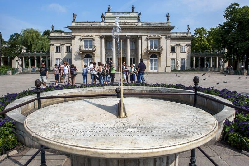 Туристы стоят рядом с солнечными часами на парке Lazienki в Варшаве в Польше стоковое фото rf