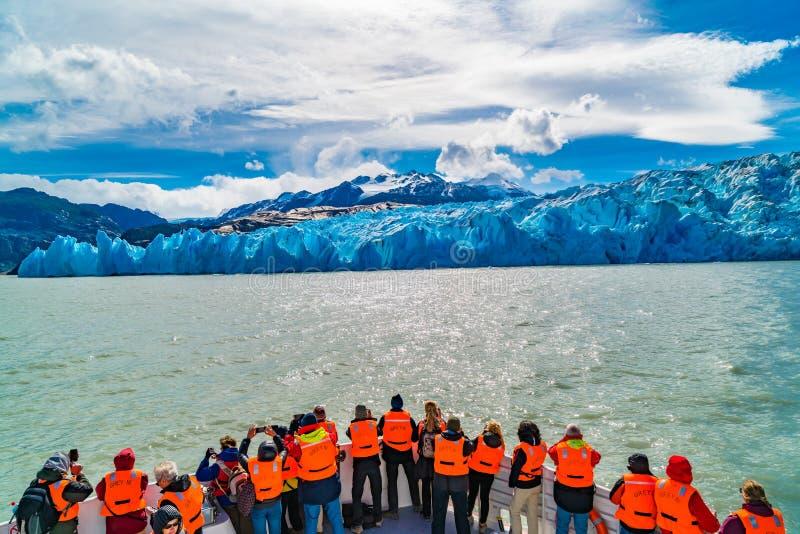 Туристы с оранжевыми спасательными жилетами цвета на отклонении экскурсионного катера к серому леднику стоковое фото