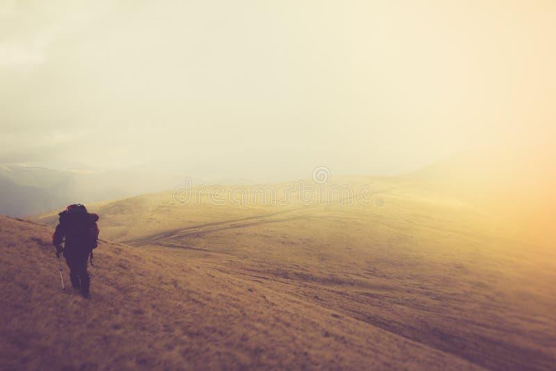 Туристы с рюкзаками взбираются к верхней части горы в тумане стоковое изображение rf