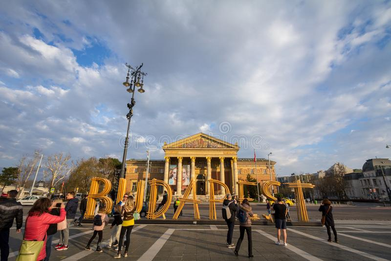 Туристы фотографируя перед знаком Будапешта с Muscarnok Hall искусств в предпосылке на героях квадратном Hosok Tere стоковая фотография