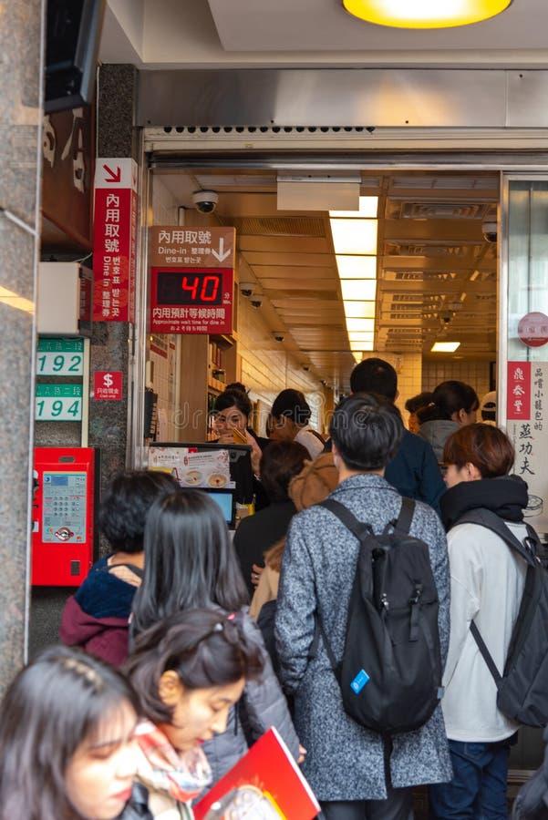 Туристы queuing на первоначальном ресторане mainstore Tai Fung Din стоковое изображение