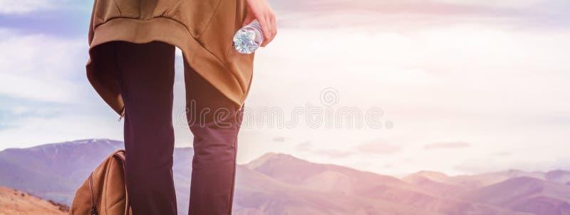 Турист девушки стоит на холме с бутылкой питьевой воды в руке Ноги конца-вверх путешественника и рюкзака стоковая фотография rf