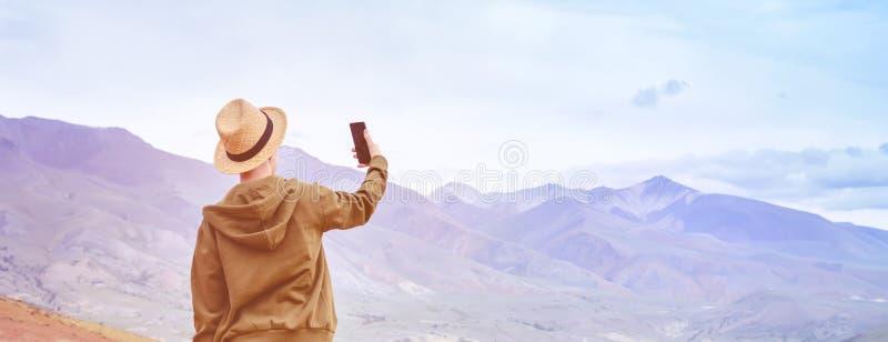 Турист девушки туристский в шляпе делает панораму из голубых гор на умном телефоне Тонизировать восход солнца стоковое изображение