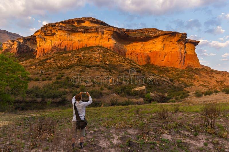 Турист держа умный телефон и принимая фото на сценарную скалу загоренную светом захода солнца в величественных гористых местностя стоковое изображение
