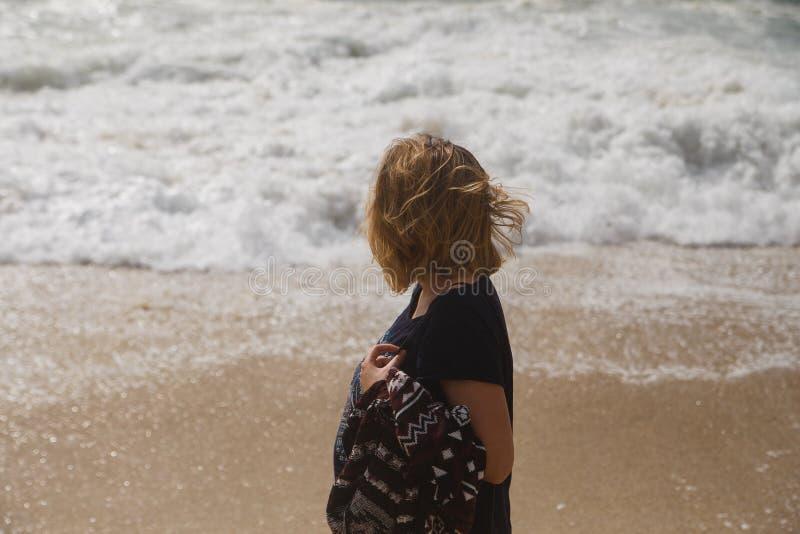 Турист женщины идя на береговую линию и смотря к бурному морю стоковые фотографии rf
