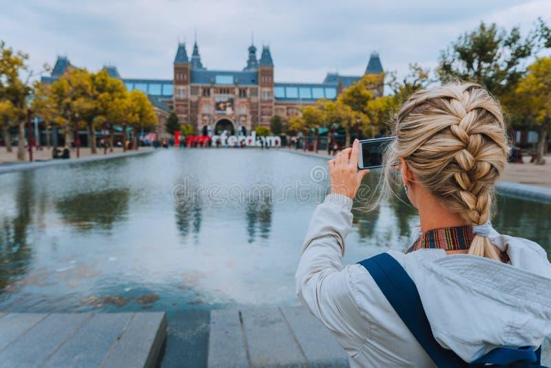 Турист женщины принимая фото Rijksmuseum в Амстердаме на мобильном телефоне Перемещение в концепции отключения города Европы стоковые изображения rf