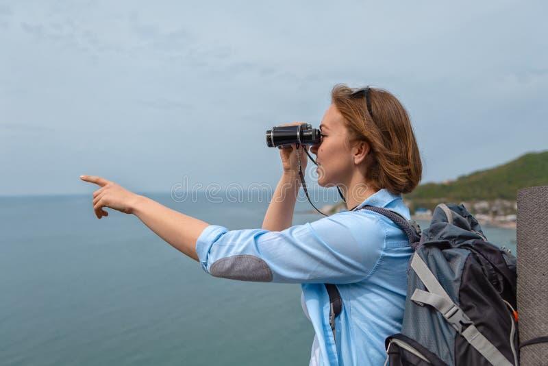 Турист женщины смотрит через бинокли и пункты к что-то с его рукой Голубое небо и море на заднем плане стоковое изображение