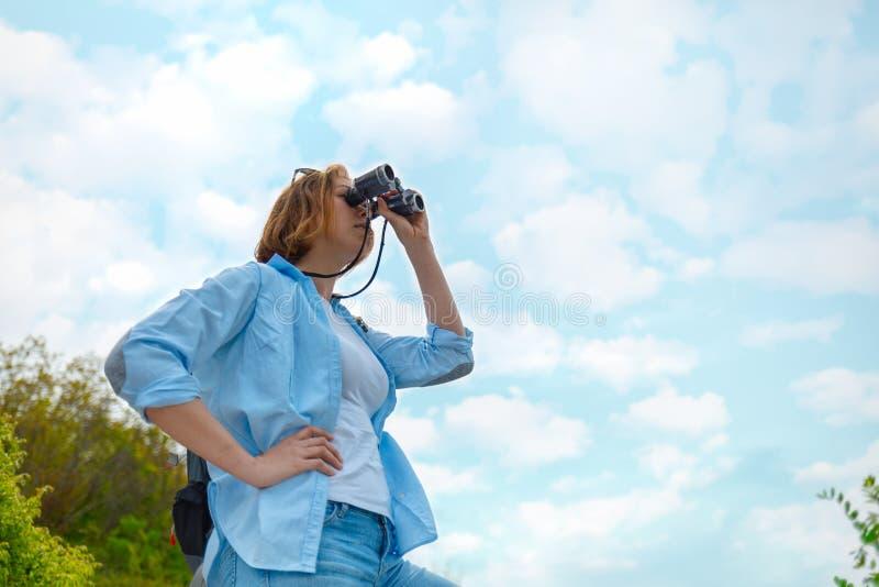 Турист женщины смотря через бинокли На заднем плане, голубое небо с облаками r стоковые фото