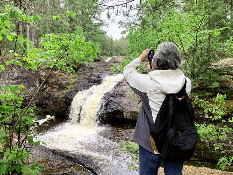 Турист женщины фотографируя водопада стоковое изображение