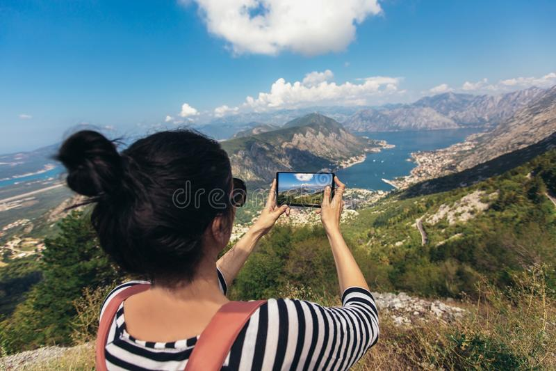Турист использует телефон для того чтобы сфотографировать ландшафт стоковые фотографии rf