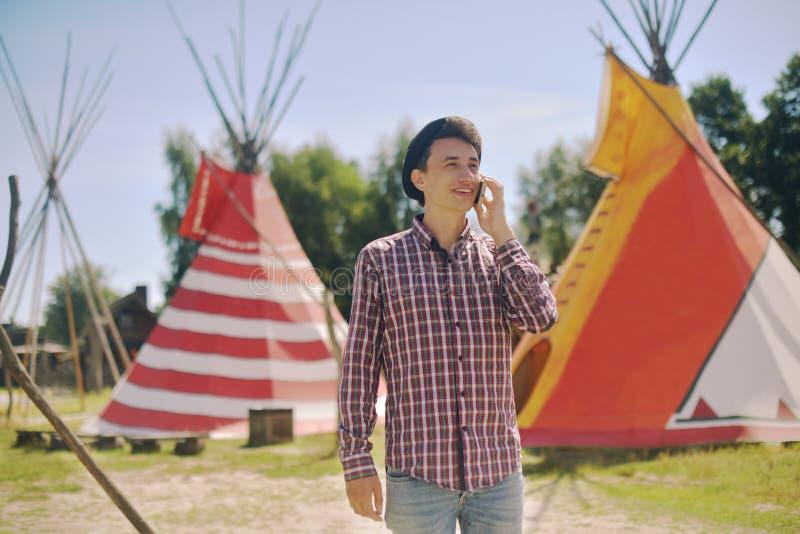 Турист молодого человека говоря на телефоне и усмехаясь на доме teepee/типи предпосылки родном индийском Человек в путешественник стоковые фото