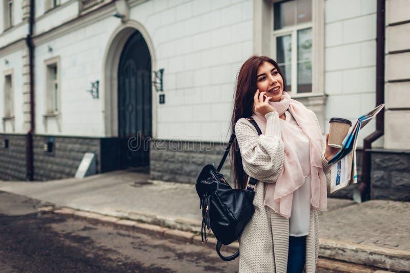 Турист молодой женщины ища правого пути использующ карту и говорящ по телефону Девушка потерянная в городе стоковое изображение