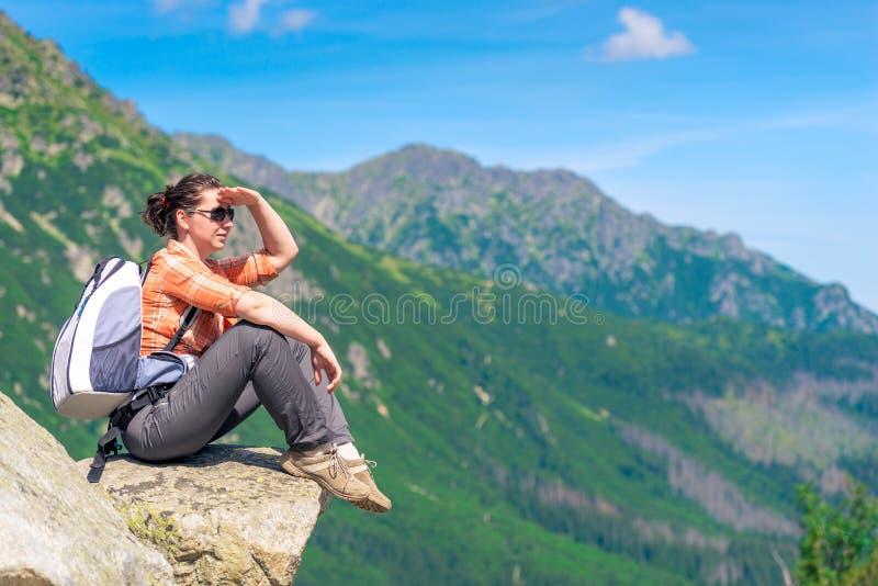турист на камне сидит ослабляет и взгляды прочь стоковые фотографии rf