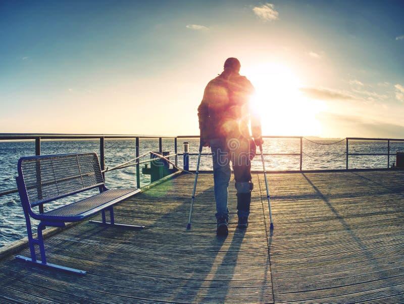 Турист на моли парома в пределах восхода солнца или захода солнца Теплые цвета стоковые фото