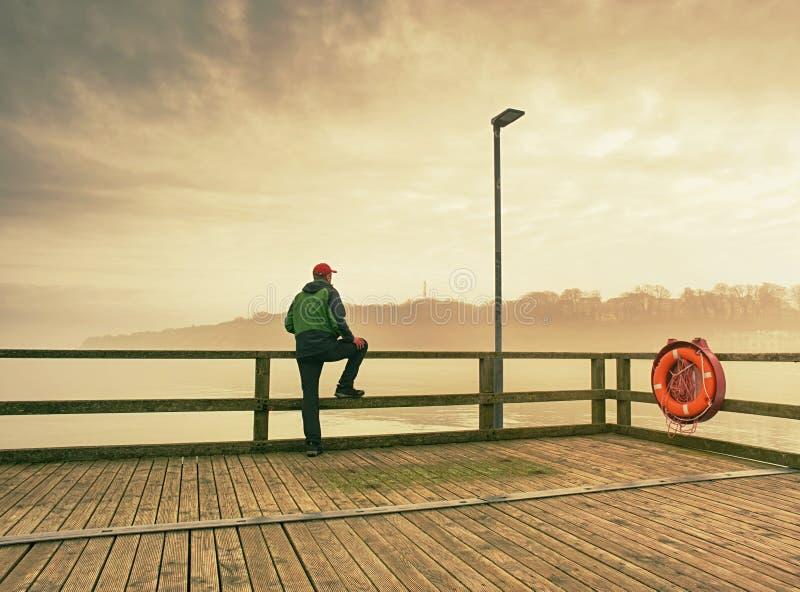 Турист на сумраке на мосте и взглядах доков afar стоковое изображение