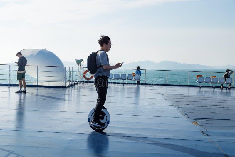 Турист на электрическом monowheel на палубе парома от Jeju к Мокпхо, Южной Корее стоковое фото rf