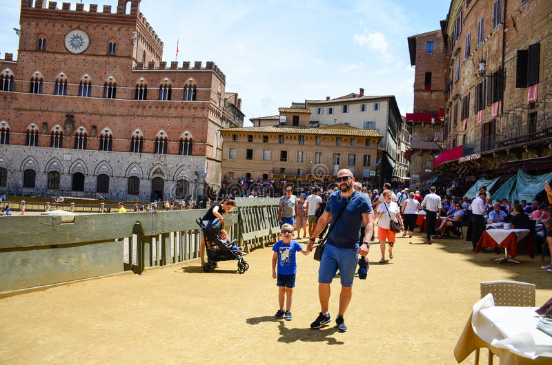 турист около Palazzo Publico в ратуше Аркады del Campo Сиены, Тосканы, Италии стоковое фото