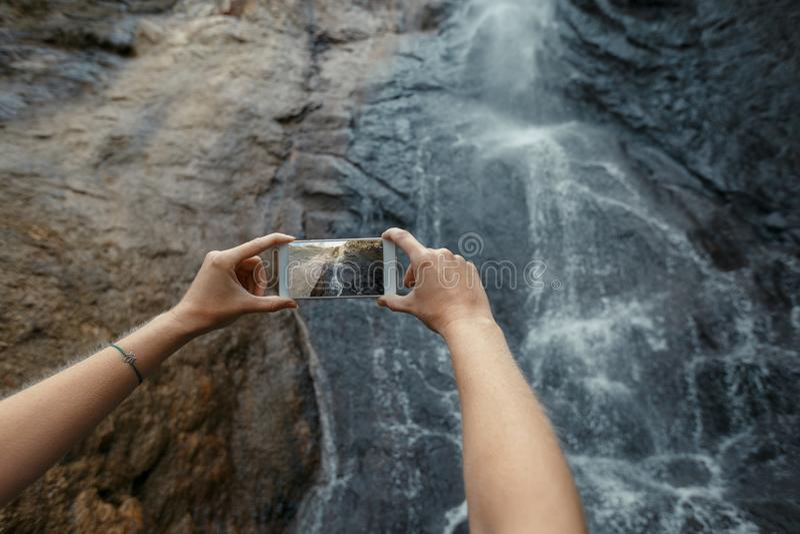 Турист принимая фото водопада с мобильным телефоном Концепция назначения приключения перемещения внешняя стоковое изображение