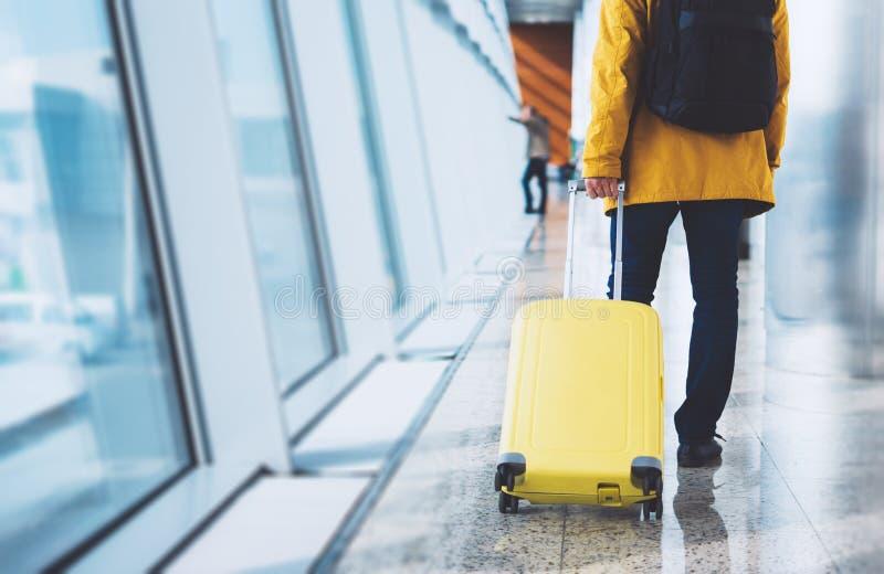 Турист путешественника в яркой куртке с желтым рюкзаком чемодана в аэропорте на небе большого окна предпосылки голубом, ожидании  стоковое изображение