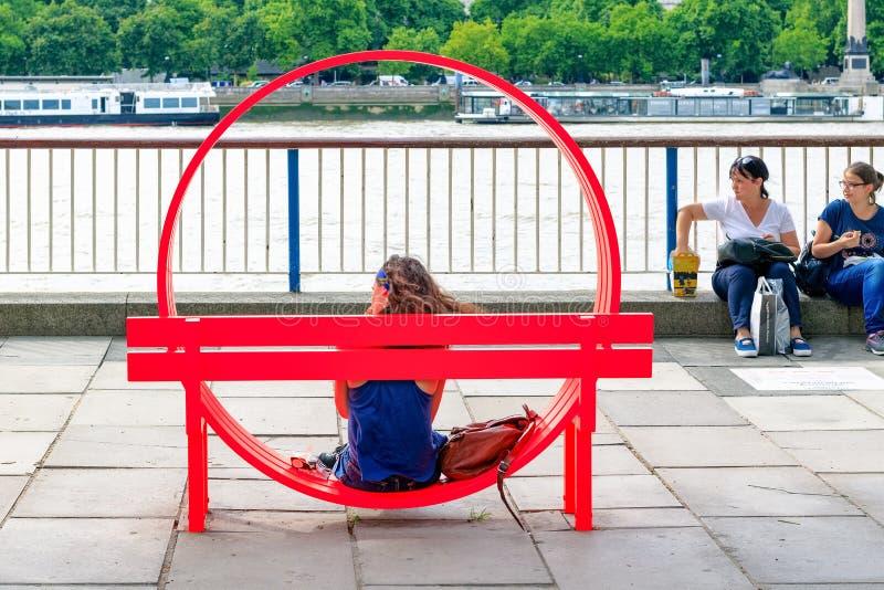 Турист сидя на одном из доработанных социальных стендов Jeppe Hein стоковое фото