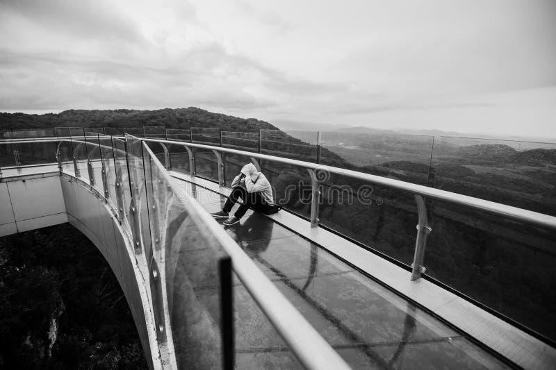 Турист сидит на пике утеса песчаника в горах стоковое фото rf