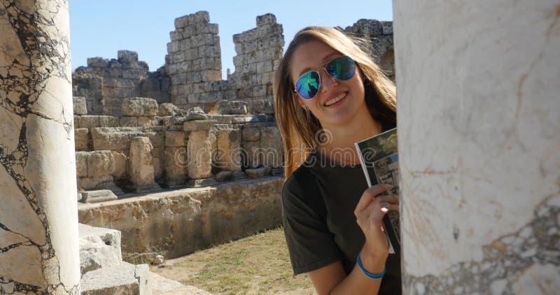 Турист смотрит вне старый столбец в музее древнего города под открыты стоковые изображения