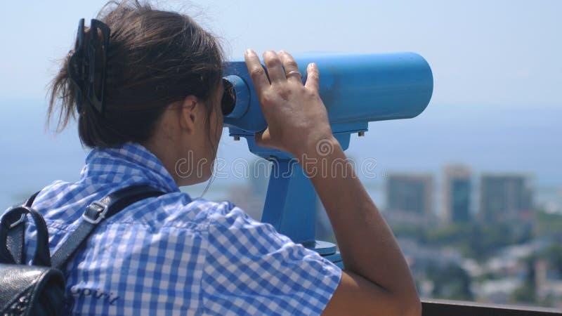 Турист смотря через бинокли на Сочи Молодая женщина при рюкзак смотря через бинокли от башни высокой стоковое изображение