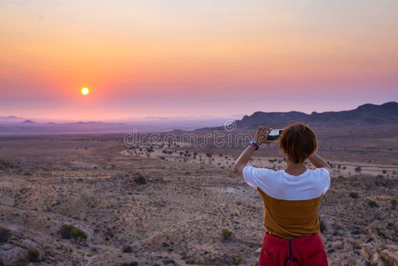 Турист фотографируя с smartphone сногсшибательный взгляд неурожайной долины в пустыне Namib, величественной привлекательности пос стоковые изображения
