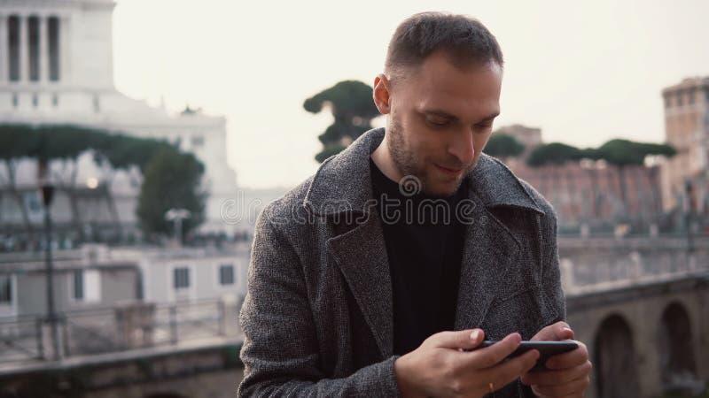 Турист человека исследует новый город, принимает фото selfie центра города на smartphone Мужчина наслаждается отключением к Риму, стоковые фото