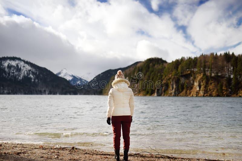 Турист Feamle наслаждается видом на озеро Alpsee, расположенным около Hohenschwangau и замков Нойшванштайна Бавария Германия стоковые фото