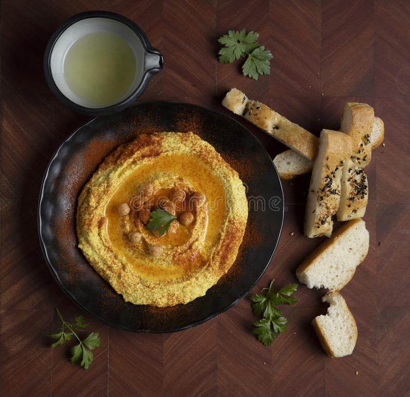 Турмерический хумус подается на деревянном доске с турецким хлебом и оливковым маслом стоковая фотография