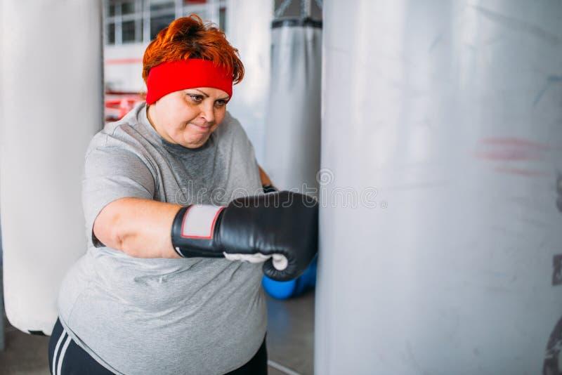 Тучная женщина в перчатках бокса работает с грушей стоковое фото