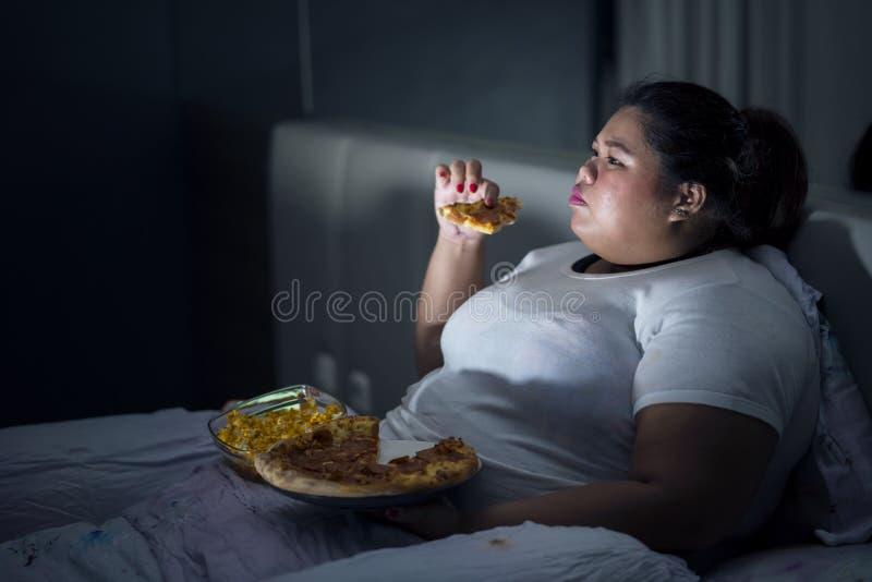 Тучная женщина есть пиццу на кровати стоковая фотография rf