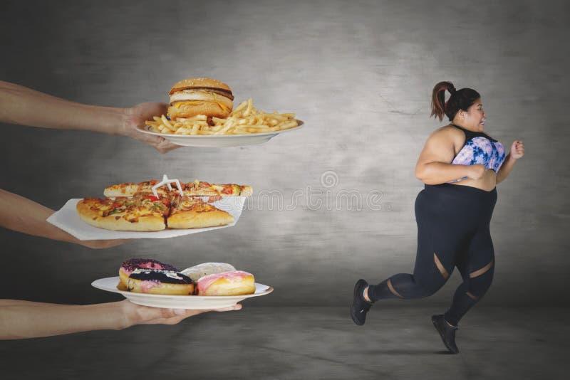 Тучная женщина избегая от нездоровой еды стоковые фотографии rf