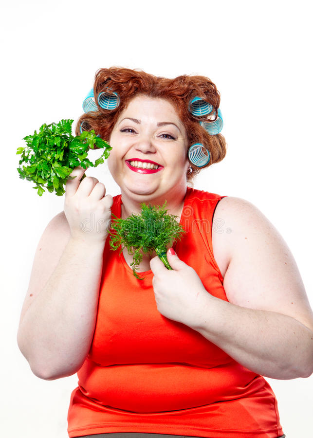 Тучная женщина с губной помадой чувственности красной в curlers на диете держа петрушку и укроп стоковая фотография rf