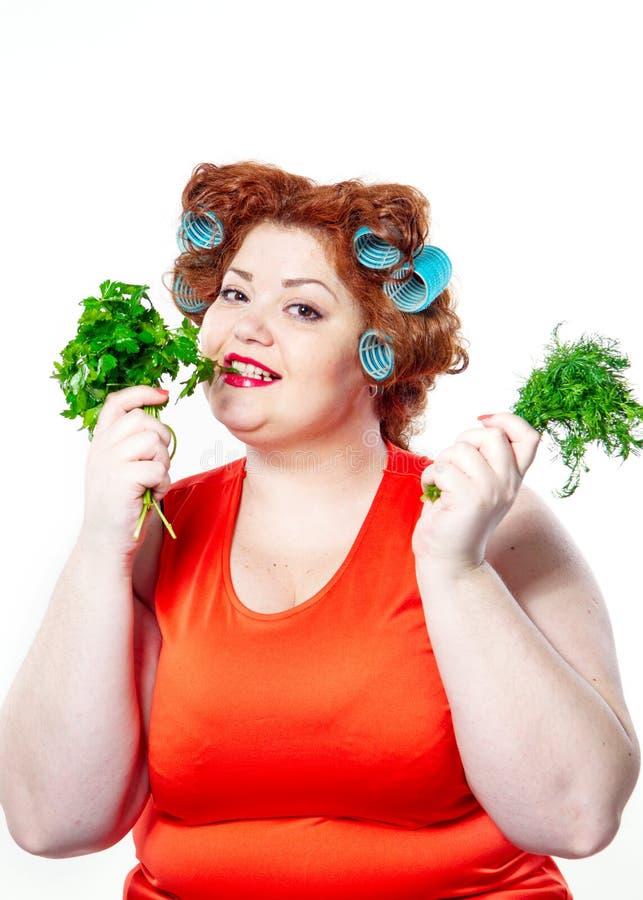 Тучная женщина с губной помадой чувственности красной в curlers на диете держа петрушку и укроп стоковые фото