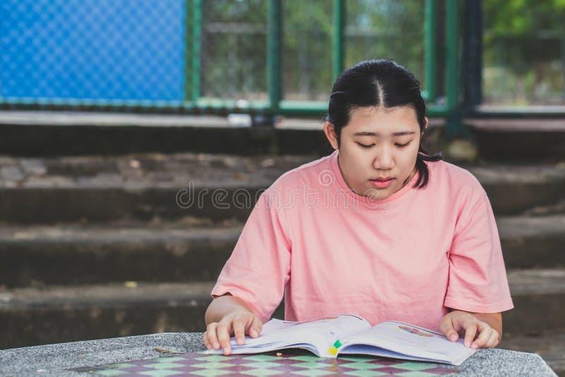 Тучное азиатское предназначенное для подростков образование книги чтения стоковое изображение rf