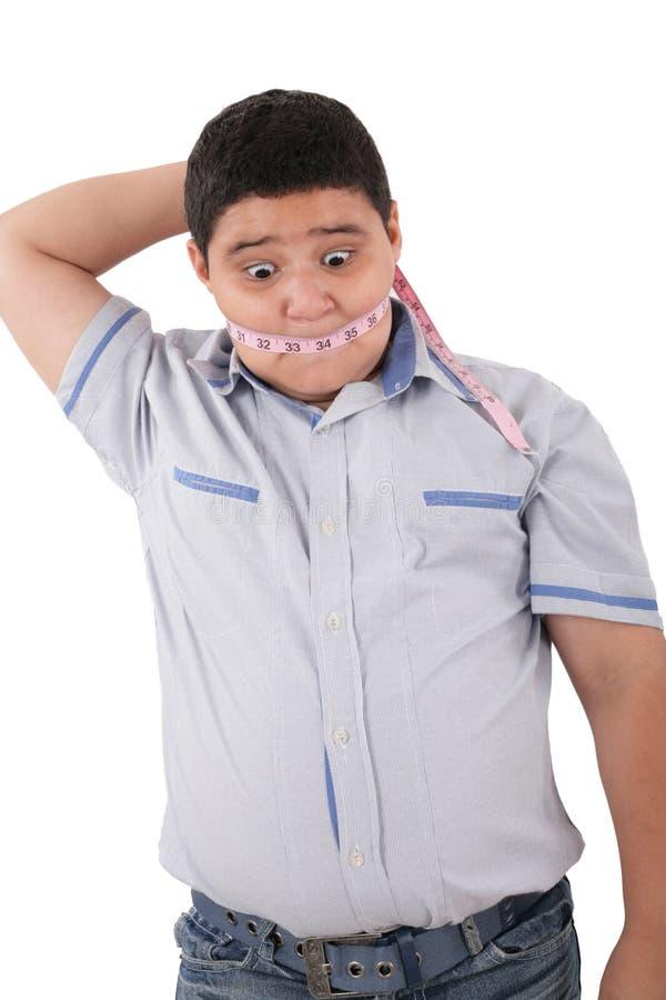 Тучный мальчик с измеряя лентой стоковое фото rf