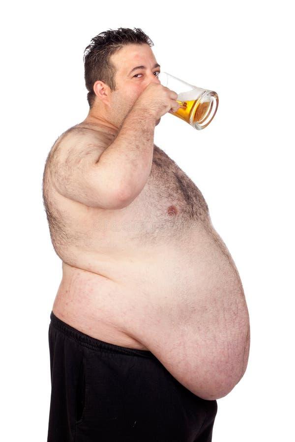 Тучный человек выпивая опарник пива стоковое изображение