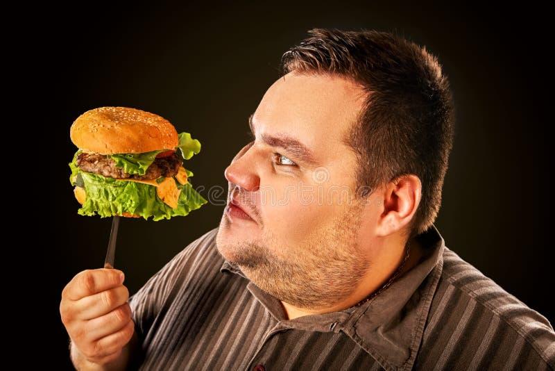 Тучный человек есть hamberger фаст-фуда Завтрак для полной персоны стоковое фото