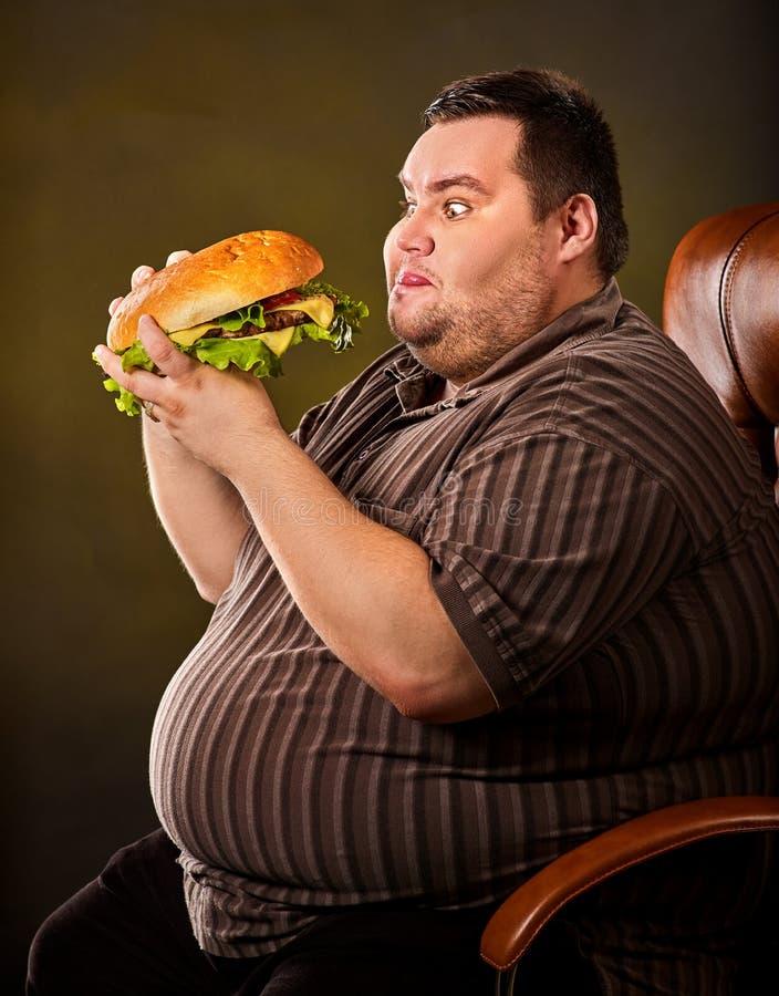Тучный человек есть hamberger фаст-фуда Завтрак для полной персоны стоковое фото rf