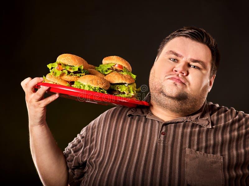 Тучный человек есть hamberger фаст-фуда Завтрак для полной персоны стоковые изображения